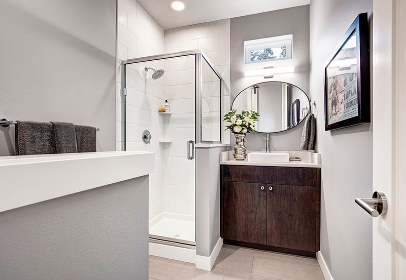 Powder-Room with shower, vanity and oval mirror